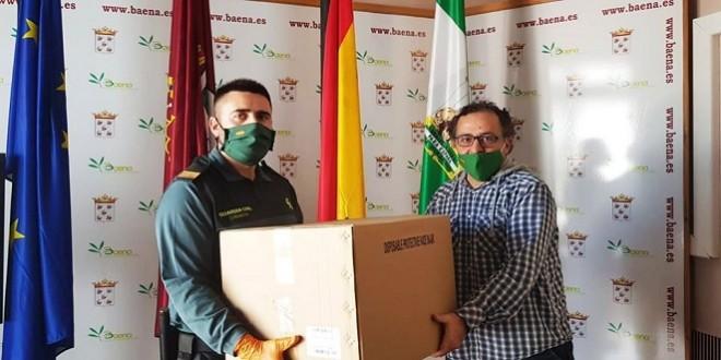 Un agente de la Guardia Civil entrega al Ayuntamiento de una caja de mascarillas quirúrgicas.