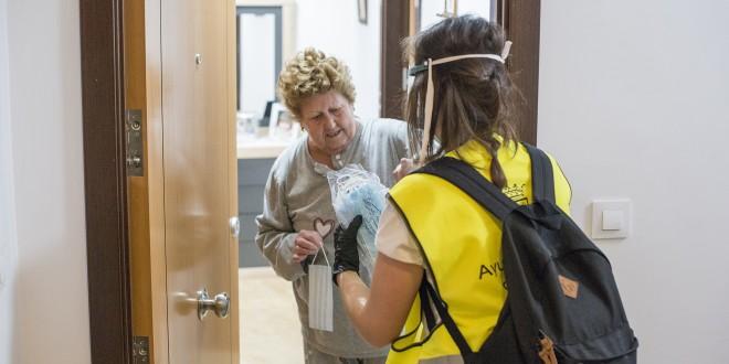 Una voluntaria entrega unas mascarillas a una vecina de Baena durante el confinamiento.